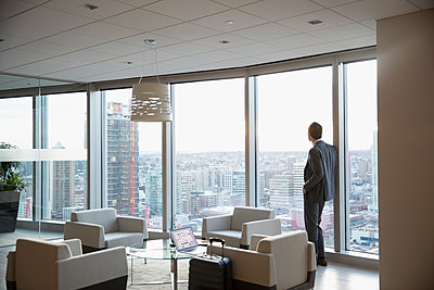 Pensive businessman with suitcase at window in highrise lounge, looking at view - p1192m1231168 by Hero Images