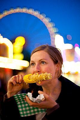 Junge Frau mit Maiskolben auf dem Jahrmarkt - p1195m987695 von Kathrin Brunnhofer