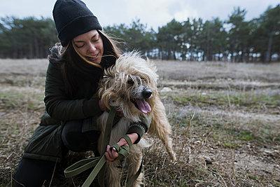 Young woman walking dog from animal shelterÊ - p1427m2174063 by Oleksii Karamanov