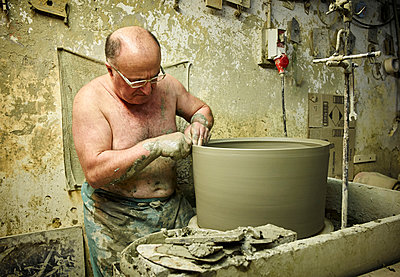 Potter in workshop working on large terracotta vase - p300m1192150 by Dirk Kittelberger