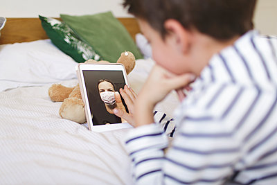 Boy lying on bed having video call on digital tablet with his mother wearng protective mask - p300m2188870 by Epiximages