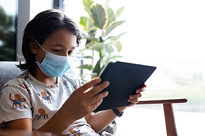 Portrait of boy with surgical mask sitting on armchair using digital tablet - p300m2189186 by Valentina Barreto