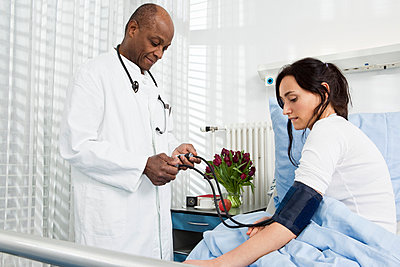 A doctor taking the blood pressure of a patient in a hospital - p301m960723f by Antenna photography