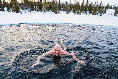Man swimming in freezing cold lake - p322m938865 von Simo Vunneli