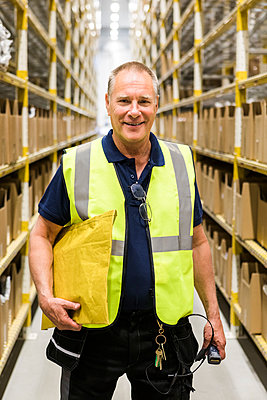 Portrait of smiling senior male worker holding package while standing on aisle at distribution warehouse - p426m2018823 by Maskot