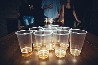 Friends playing beer pong at party - p555m1412845 by Inuk Studio