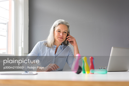 Mature businesswoman on the phone playing with pins on desk in office - p300m2155601 by Robijn Page