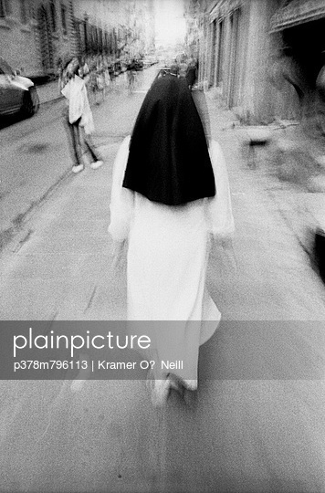 Nun walking along street - p378m796113 by Kramer O'Neill