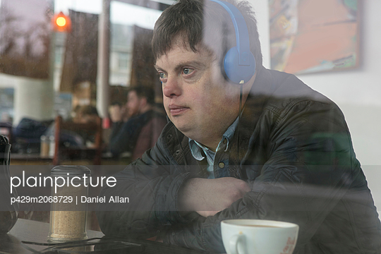 Man with down syndrome using headphones by cafe window - p429m2068729 by Daniel Allan