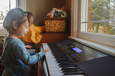 portrait of a cute little child playing piano in front of a window - p1166m2131305 by Cavan Images