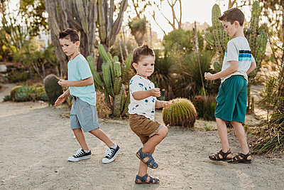 Three young brothers dancing in sunny cactus garden - p1166m2136631 by Cavan Images
