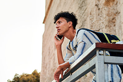Young man with afro hair is using his smartphone outdoors - p1166m2201853 by Cavan Images
