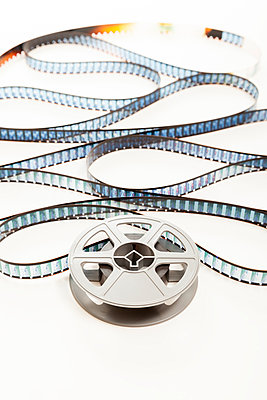 An old plastic cine film reel with film uncoiling unwinding from it  - p1302m1148574 by Richard Nixon