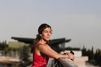 Sportswoman listening to music while leaning on railing - p300m2287432 by Eva Blanco