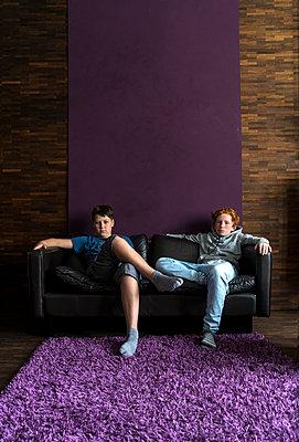 Mädchen und Junge sitzen auf dem Sofa - p427m1465444 von R. Mohr