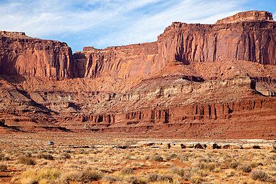 Kleinbus auf einer Schotterpiste vor einer Steilwand, Utah, USA - p756m2253320 von Bénédicte Lassalle