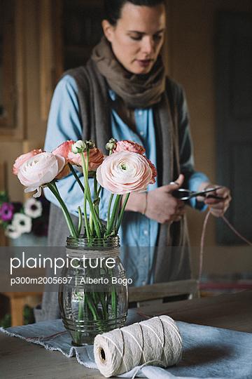 Woman arranging fresh flowers, cutting cord - p300m2005697 von Alberto Bogo