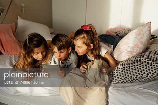 Children on bed using digital tablet - p312m2174996 by Lisa Öberg