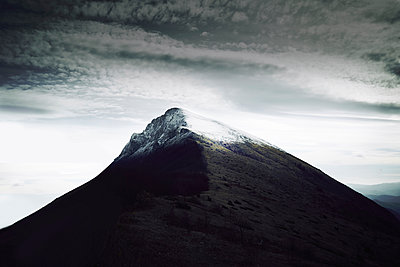 Scenic view of mountain against cloudy sky during winter - p1166m2105881 by Cavan Images