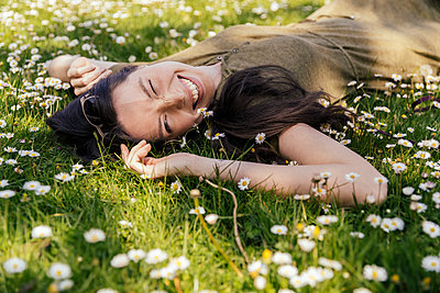 Happy woman enjoying her free time while lying on grass with daisies - p300m2199284 by Mareen Fischinger