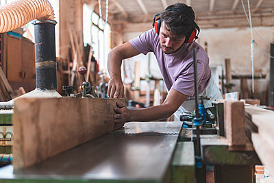 Young male craftsperson holding wooden plank on workbench while working in workshop - p300m2252601 by Josu Acosta