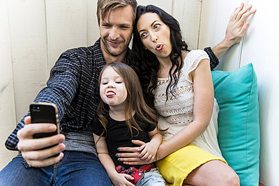Family taking selfie with cell phone - p555m1311504 by Andie Mills
