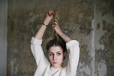 Junge Frau spielt mit ihren blonden Haaren - p586m953881 von Kniel Synnatzschke