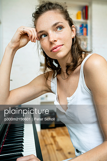 young woman sitting at the piano, smiling - p300m2156601 by Peter Scholl