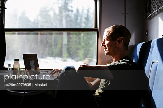 Businessman using laptop while sitting by window in train - p426m2279835 by Maskot