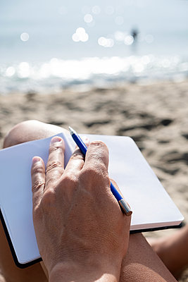 Man with a notebook on the beach - p1423m2125765 by JUAN MOYANO
