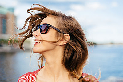 Portrait of smiling woman with blowing hair wearing sunglasses - p300m1101198f by Boy photography