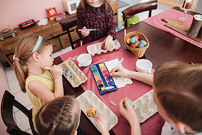 Children painting Easter eggs on table at home - p300m2103424 by Katharina Mikhrin
