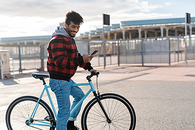 Young man wearing hooded shirt smiling while using mobile phone standing with bicycle on road - p300m2243679 by COROIMAGE