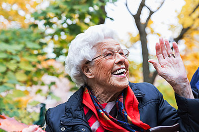 Happy senior woman gesturing while looking away in park during autumn - p426m1468252 by Maskot