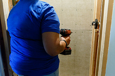Black woman holding drill near wall - p555m1504173 by Roberto Westbrook