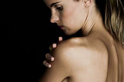 Young woman touching her bare shoulder - p623m1506977 by Frederic Cirou