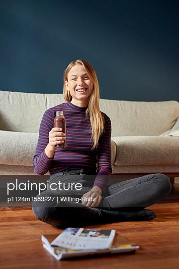 Junge Frau entspannt sich mit einem Getränk - p1124m1589227 von Willing-Holtz