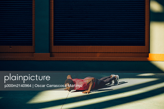 Young sportive man doing pushups outdoors - p300m2140964 by Oscar Carrascosa Martinez