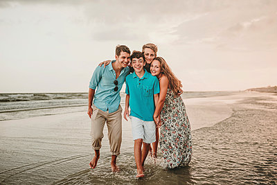 Portrait of happy siblings standing at beach against sky during sunset - p1166m2011187 by Cavan Images