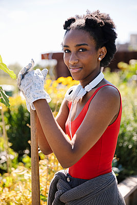 Portrait confident young woman in sunny community garden - p1192m2130185 by Hero Images
