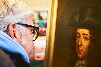Man with glasses looks at the portrait of a painting in an exhibition - p1312m2082209 by Axel Killian