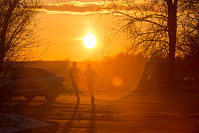 Silhouette of two joggers in winter at sunset - p300m1449446 by Konstantin Trubavin