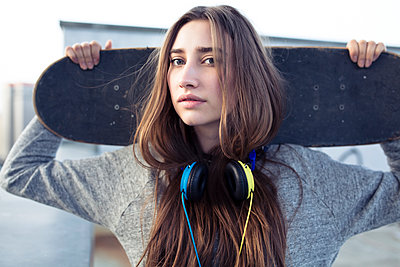 Portrait of serious young woman with skateboard and headphones - p300m2104452 by Philipp Nemenz