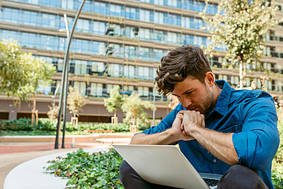 Businessman thinking while looking at laptop against office building - p300m2226765 by Valentina Barreto