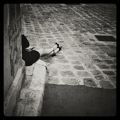 Young woman sits on cobbled street - p567m1095633 by Alexis Bastin