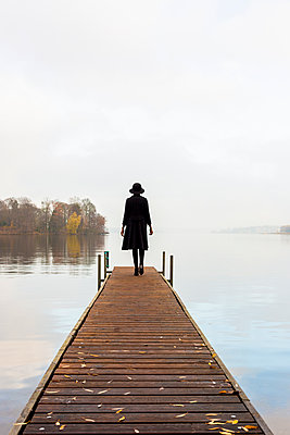 Young woman with hat on boardwalk by the lake - p975m2228197 by Hayden Verry