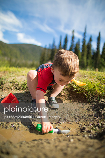 Toddler boy shovelling in a muddy puddle. - p1166m2094896 by Cavan Images