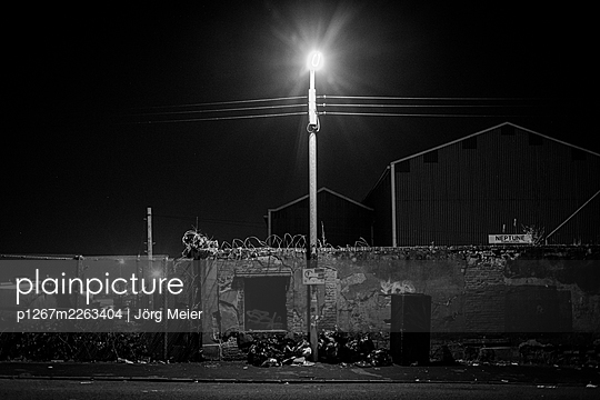 Street lamp lights up a wall with barbed wire - p1267m2263404 by Jörg Meier