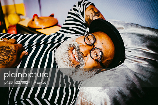 Portrait of smiling senior man winking while lying at home - p426m2279827 by Maskot