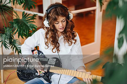 Junge Frau spielt Gitarre - p586m1200157 von Kniel Synnatzschke
